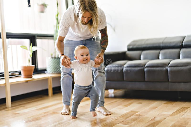 Дочь младенца помощи отца предпринять первые шаги дома стоковое фото rf