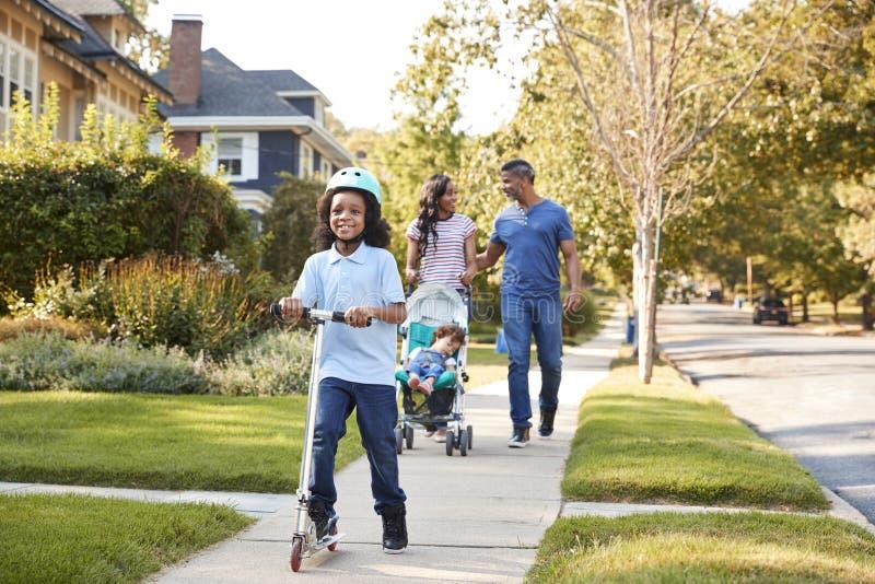 Дочь нажима пар в прогулочной коляске как сын едет самокат стоковое изображение