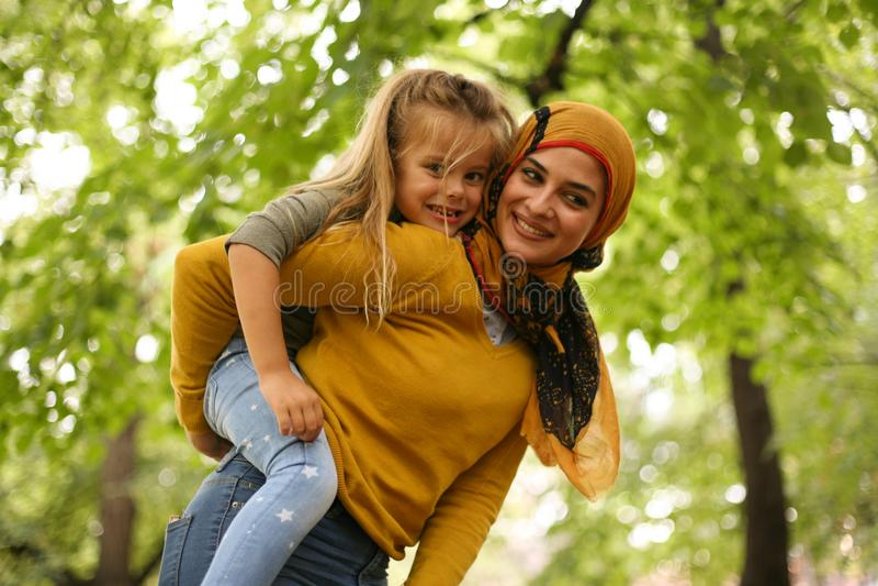 Дочь нося матери на автожелезнодорожных перевозках muslim стоковое фото