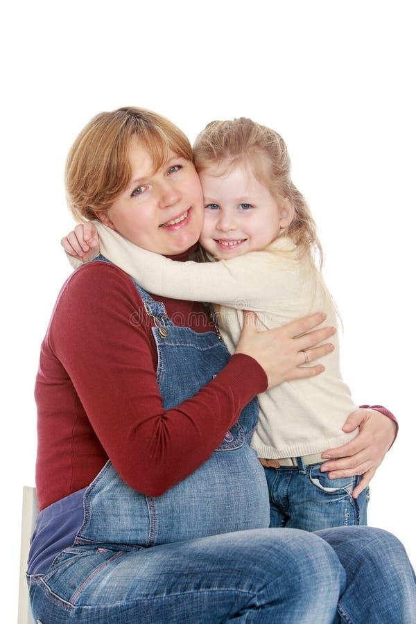 Дочь обнимая беременную маму стоковая фотография