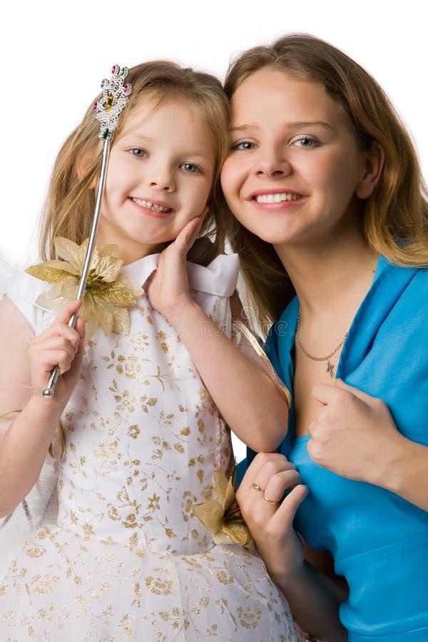 дочь одевает праздничную мать стоковые фото