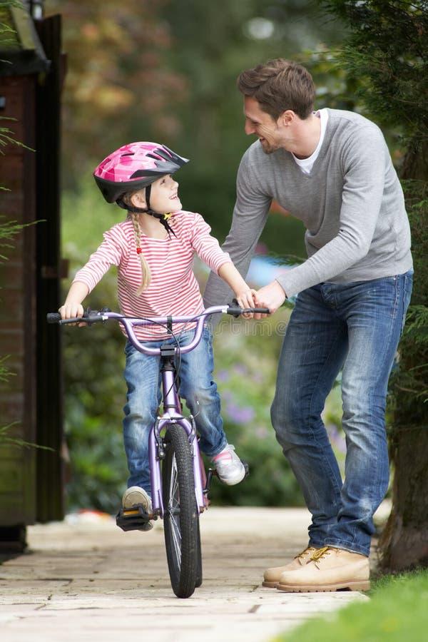 Дочь отца уча для того чтобы ехать велосипед в саде стоковое изображение