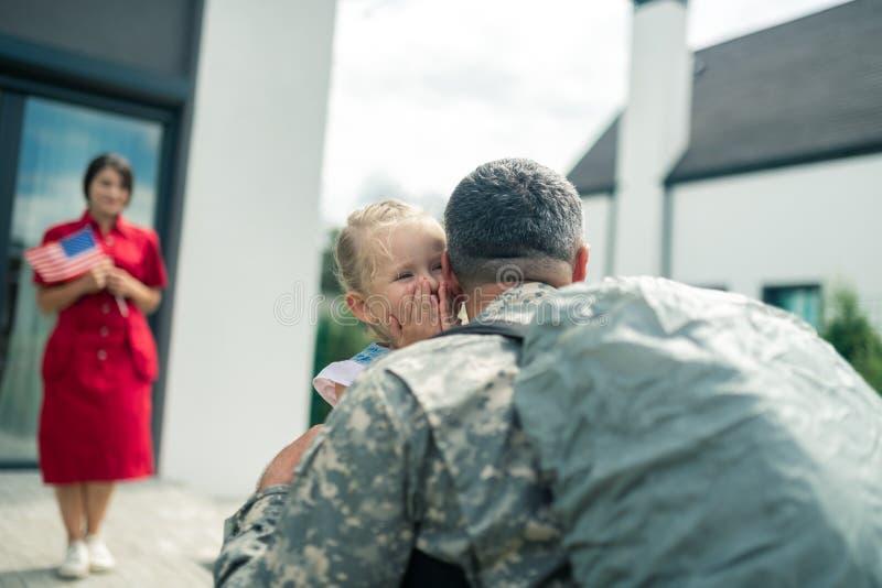 Дочь плачет из-за счастья, видя отца дома стоковая фотография