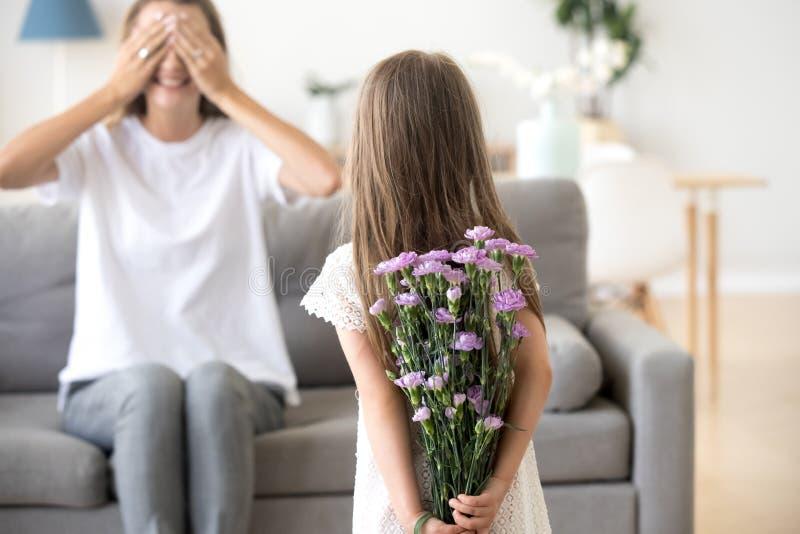 Дочь подготовленная для цветков мамы пряча его за ее задней частью стоковая фотография rf