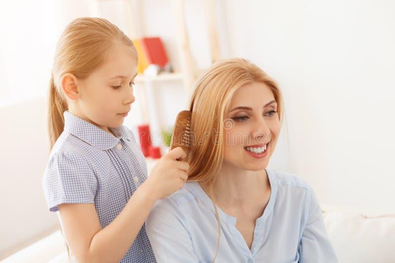 Дочь расчесывая волосы матери стоковая фотография rf