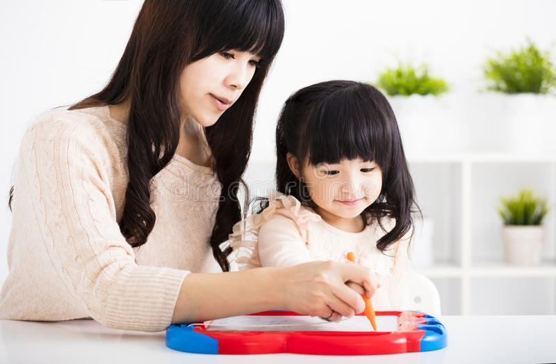 Дочь ребенка порции матери или учителя к записи стоковые изображения