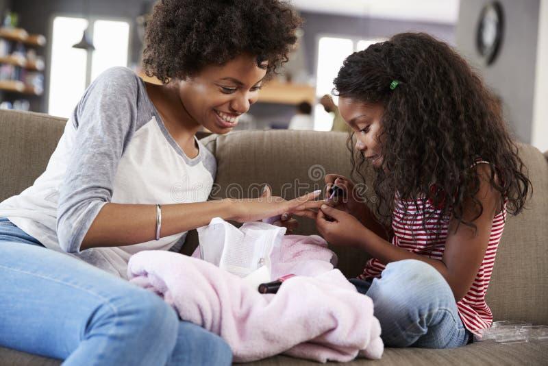 Дочь сидя на софе дома крася ногти ` s матери стоковое изображение