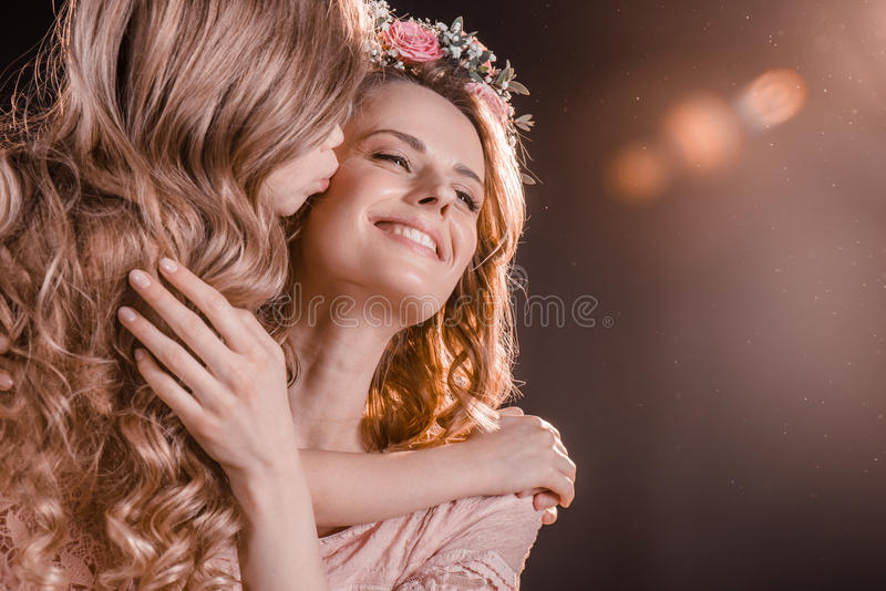 Дочь целуя усмехаясь мать на черноте стоковое изображение rf