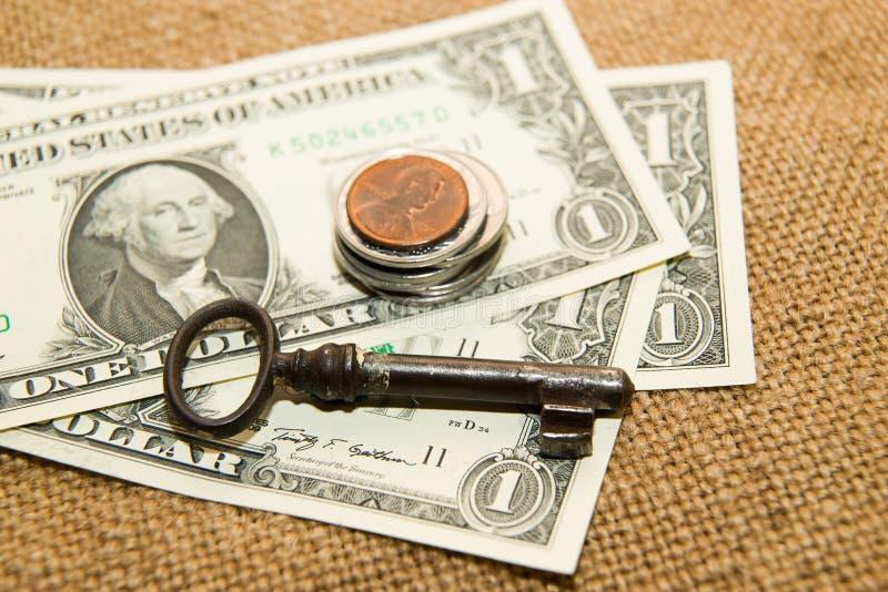 Доллары США банкнот, монеток и ключа на старой ткани стоковое изображение