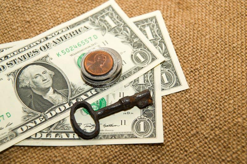 Доллары США банкнот, монеток и ключа на старой ткани стоковое фото