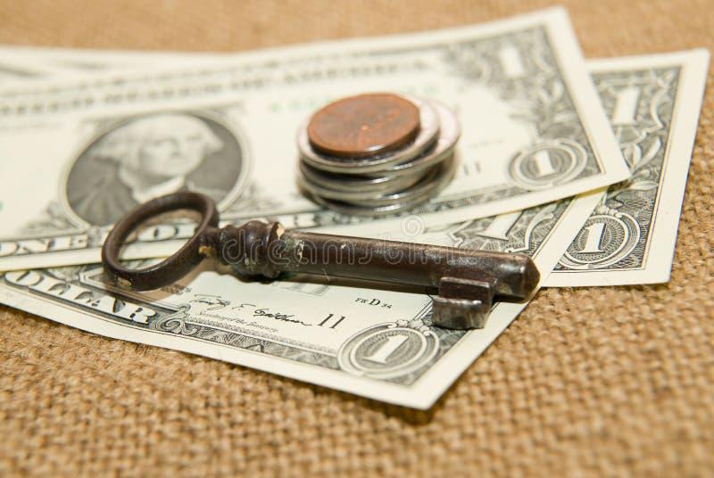 Доллары США банкнот, монеток и ключа на старой ткани стоковое фото rf