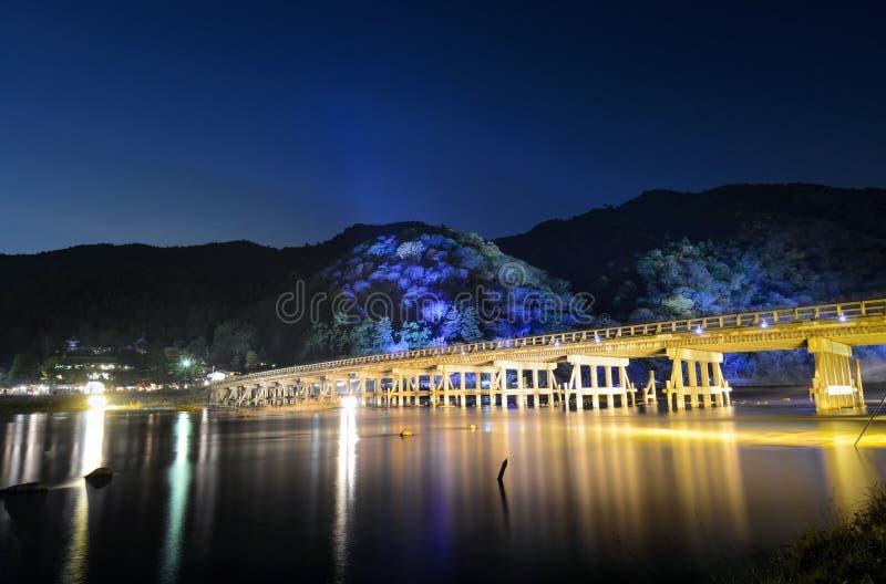 Долгая выдержка освещений ночи на мосте и горах Togetsu во время фестиваля Arashiyama Hanatouro в Киото стоковые фотографии rf