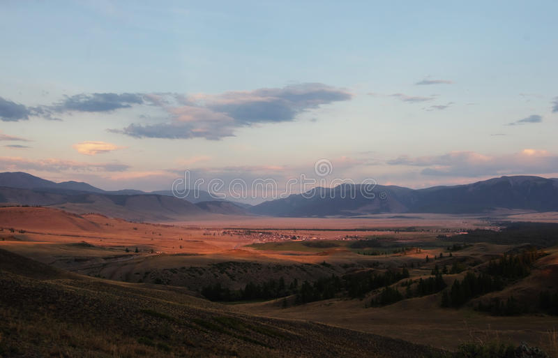 Долина степи горы на предпосылке деревни на заходе солнца стоковые изображения rf