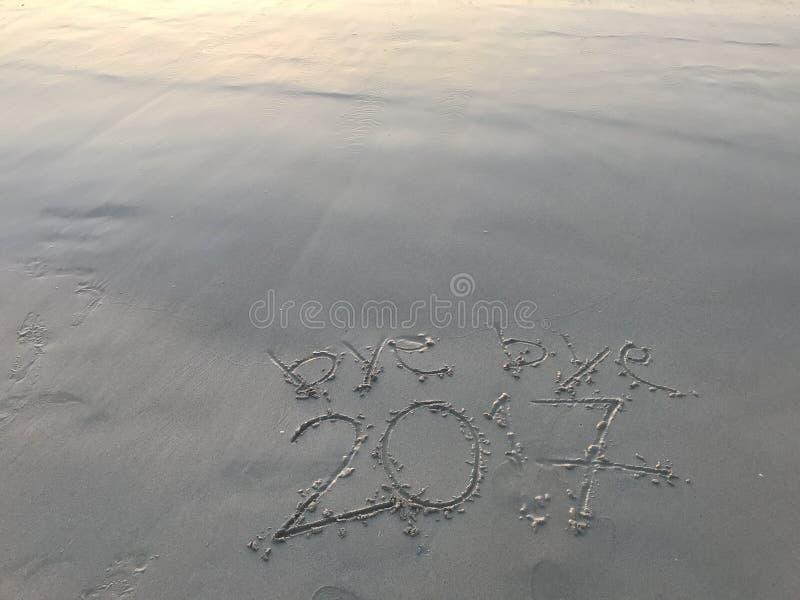 До свидания 2017 на ясном пляже песка когда восход солнца стоковые фото