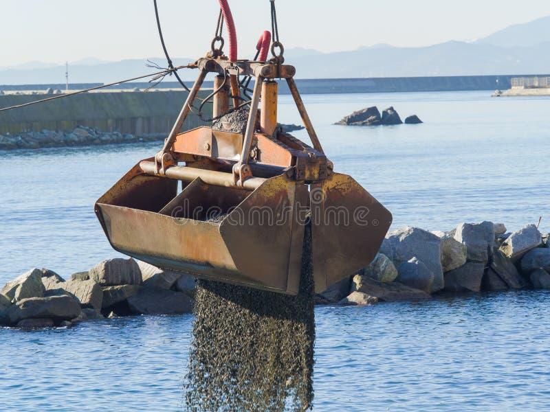 Драгируйте двухстворчатый грейферный ковш разгржая гравий в воде порта стоковые изображения
