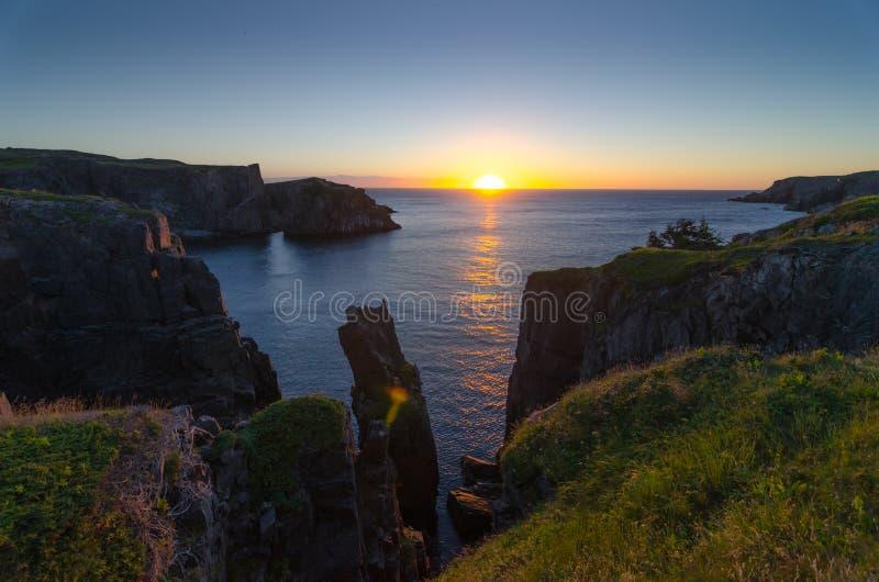 Драматические скалы восхода солнца на бухте Ньюфаундленде Джона кабеля Рассвет над Атлантическим океаном стоковая фотография rf