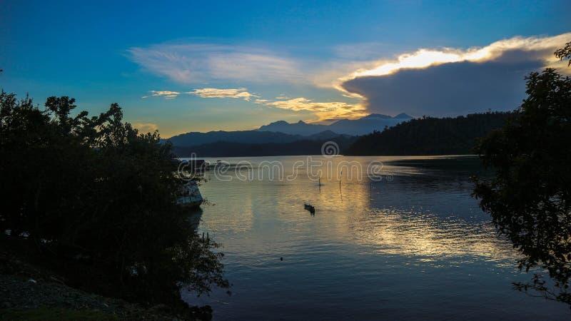 Драматический взгляд захода солнца с предпосылкой моря горы стоковое изображение