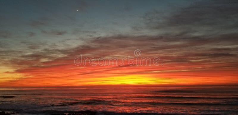 Драматический заход солнца над Тихим океаном - волнами разбивая на утесах стоковые фотографии rf