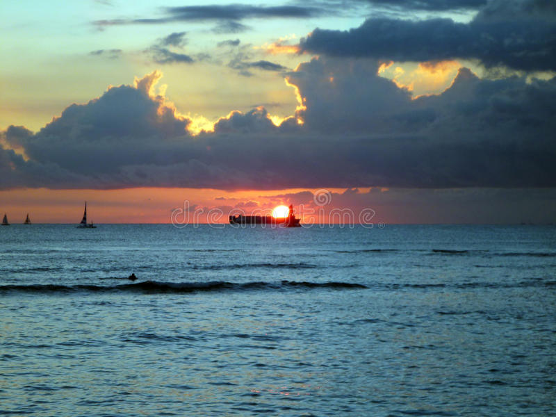 Драматический заход солнца над шлюпкой груза под облаками и reflectin стоковая фотография rf