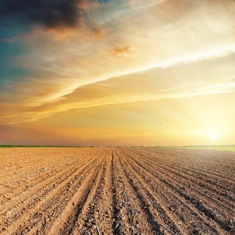 Драматический оранжевый заход солнца и вспаханное поле стоковое изображение rf