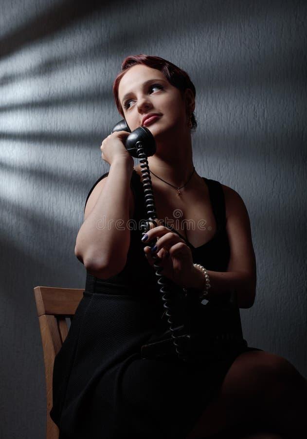 Драматический портрет красивой женщины с старым черным телефоном стоковая фотография