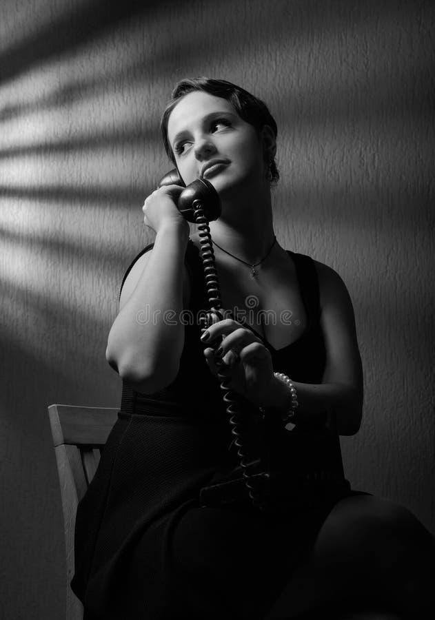 Драматический портрет красивой женщины с старым черным телефоном стоковые изображения