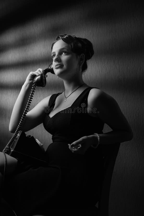 Драматический портрет красивой женщины с старым черным телефоном стоковые фото