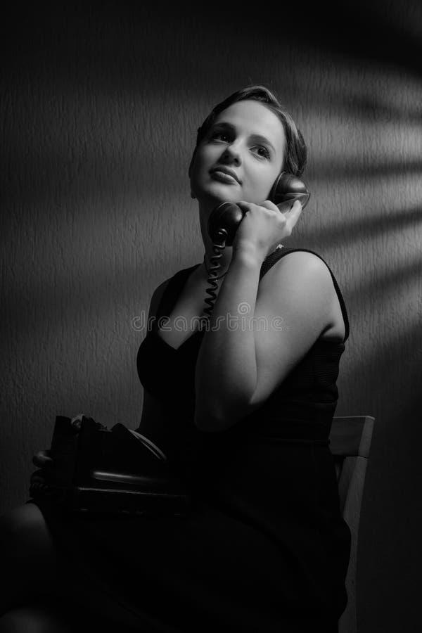 Драматический портрет красивой женщины с старым черным телефоном стоковое изображение rf