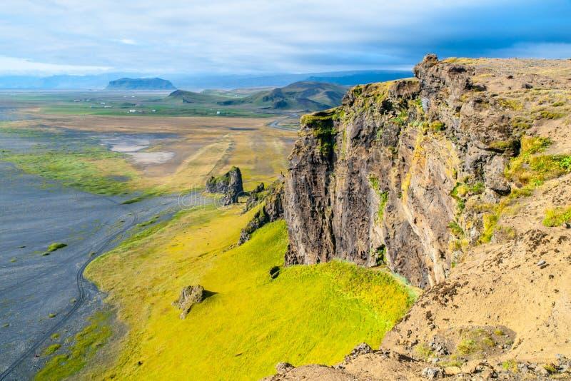 Драматический скалистый ландшафт береговой линии с зелеными крутой склон, одичалыми утесами и черным пляжем, Исландией стоковые изображения