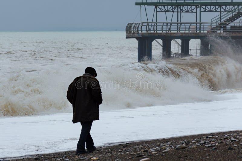 Драматический, штормовая погода, сиротливый старик идя вдоль побережья стоковое изображение rf