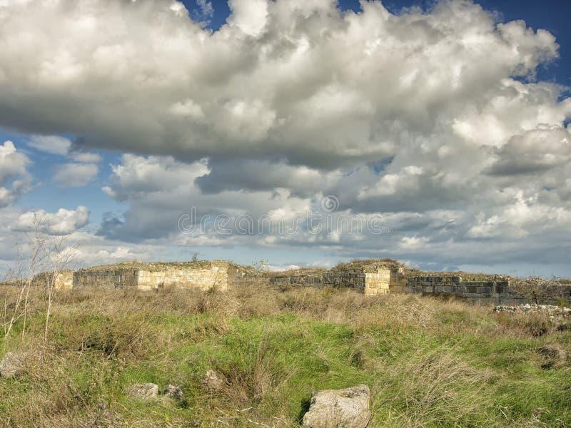 Драматическое голубое небо с белыми облаками над руинами колонии древнегреческия Histria, на берегах Чёрного моря Histria стоковая фотография rf