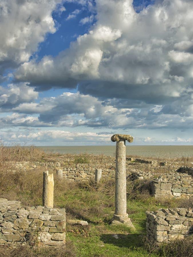 Драматическое голубое небо с белыми облаками над руинами столбца древнегреческия на Histria, на берегах Чёрного моря Histria t стоковые изображения rf