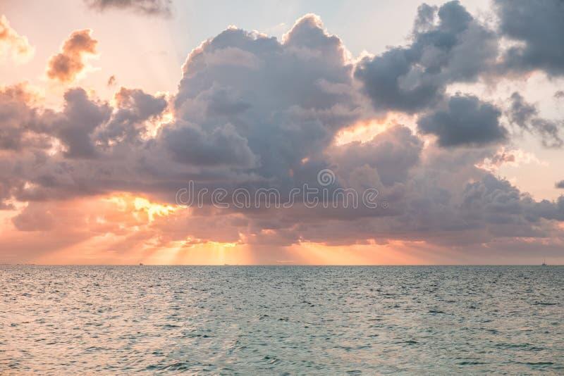 Драматическое небо во время захода солнца над водой - сценарного захода солнца над ocea стоковое фото