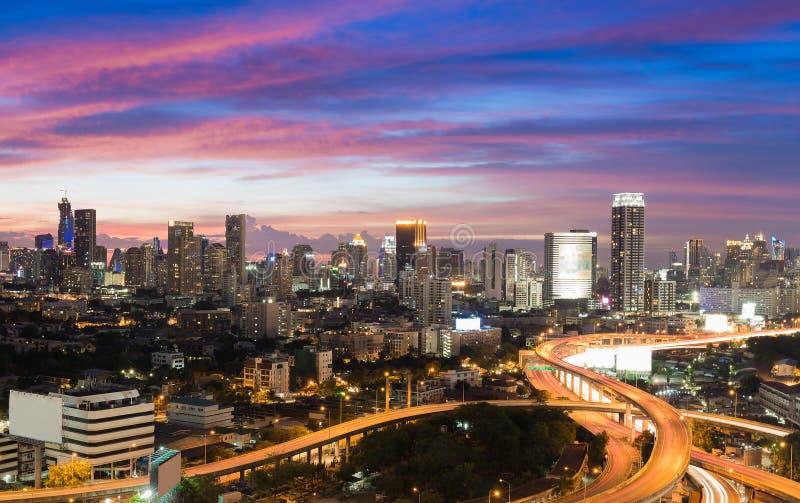 Драматическое небо после захода солнца повышенного шоссе с предпосылкой офисного здания города стоковое изображение rf