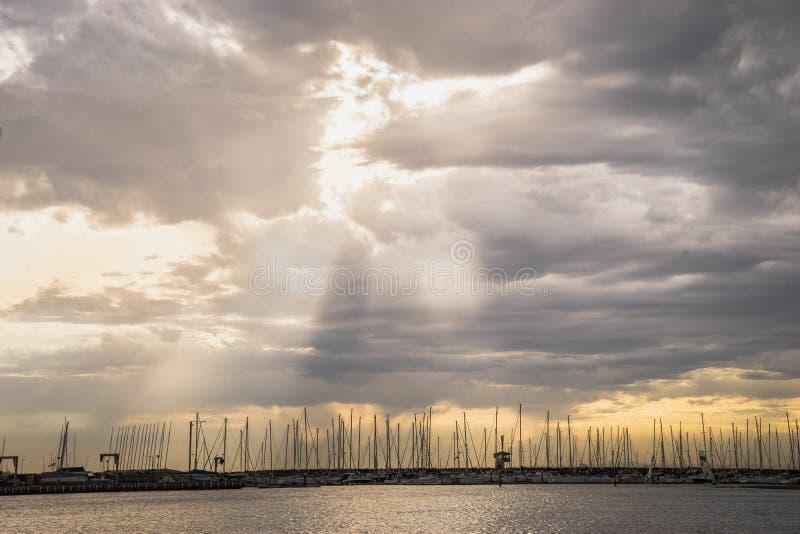 Драматическое пасмурное небо захода солнца с лучем светового луча солнца над шлюпкой j стоковая фотография rf