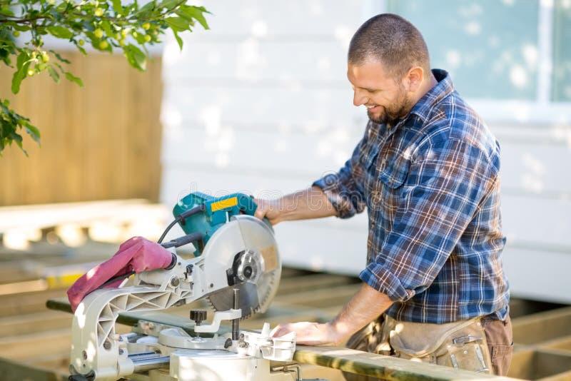Древесина вырезывания плотника используя таблицу увидела на стоковые изображения