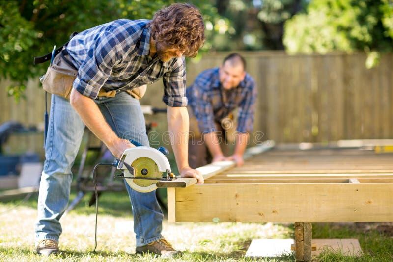 Древесина вырезывания плотника с Handheld увидела пока стоковые фотографии rf