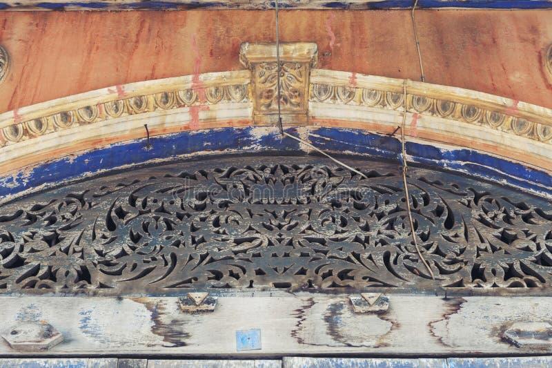 Древесина высекая и орнаменты штукатурки украшая над входной дверью классического китайско-португальского здания, Yasothon, Таила стоковые фото