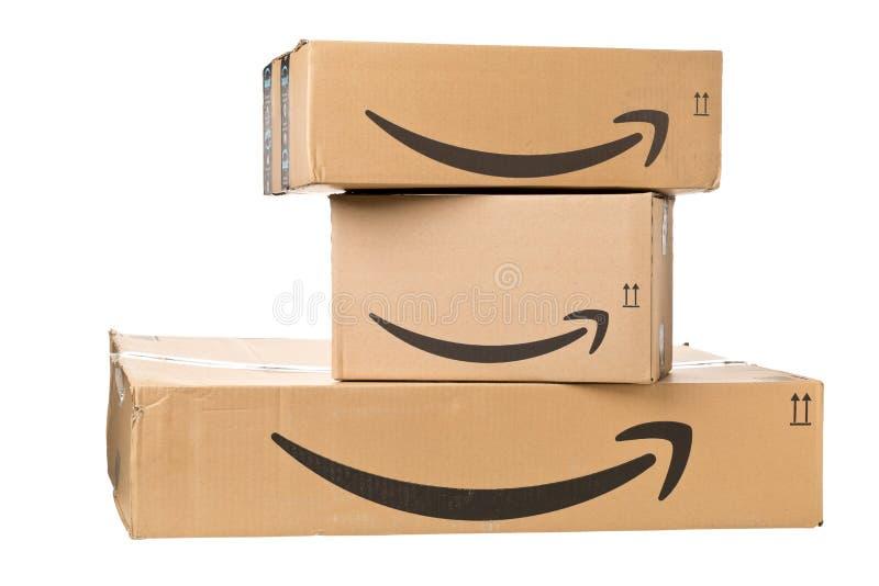 ДРЕЗДЕН, ГЕРМАНИЯ - 3-ЬЕ АПРЕЛЯ 2019: Логотип Амазонки на стоге поставленных пакетов изолированных на белой предпосылке стоковое фото rf