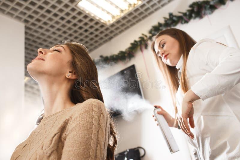 Дрессер волос распыляя с политурой к прическе ` s клиента стоковое фото rf