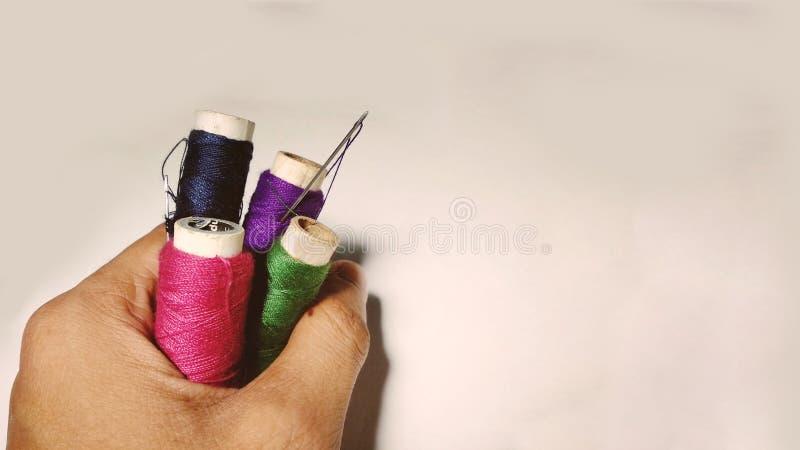 Другие цвета продевают нитку крены с иглой в руке портноя стоковое изображение rf