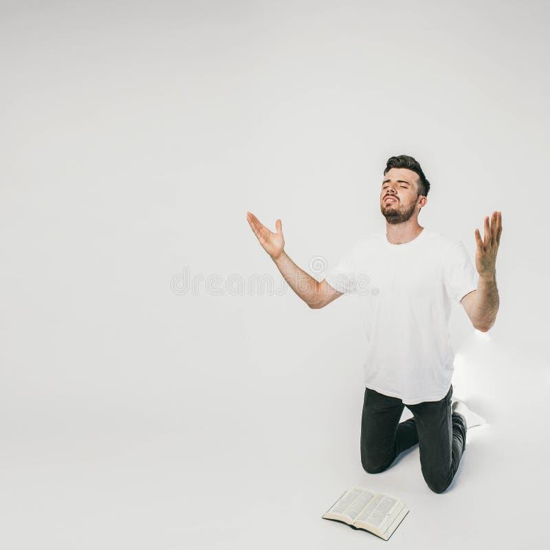 Другое изображение парня стоя на правильной позиции рамки на его коленях и моля aloud Он один в комнате но стоковые изображения