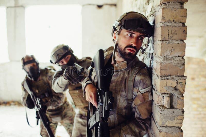 Другое изображение человека в форме стоя за стеной и ждать Попечители кудели за бородатым человеком Они стоковые фотографии rf