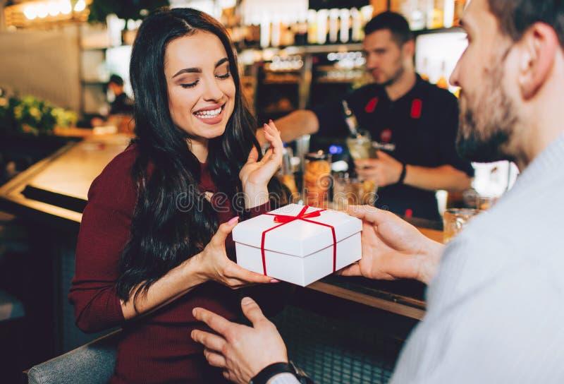 Другое изображение человека давая подарок к его любимой девушке Она принимает ее с улыбкой и удовольствием Она смотрит стоковая фотография