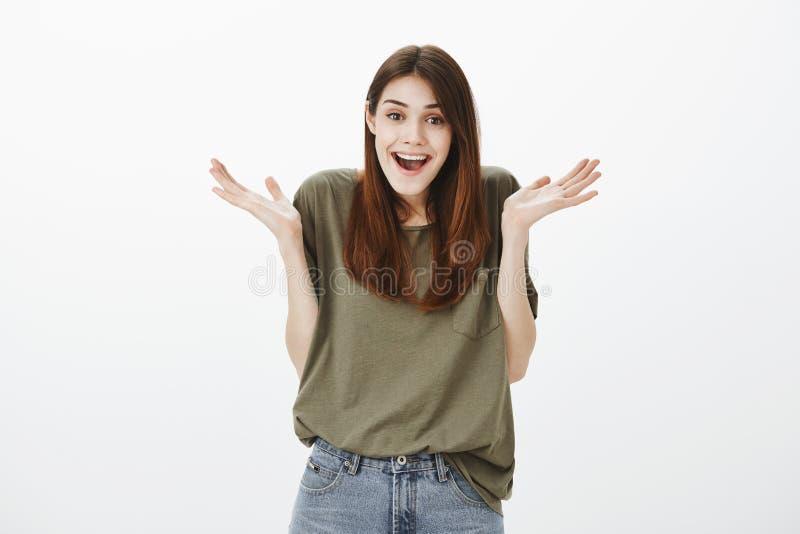 Друг присягает что она не знало о партии сюрприза Положительная счастливая европейская женщина в темн-зеленой футболке, shrugging стоковая фотография
