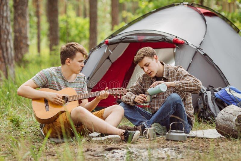 Друг 2 сидя в шатре, играет гитару и поет песни стоковое фото