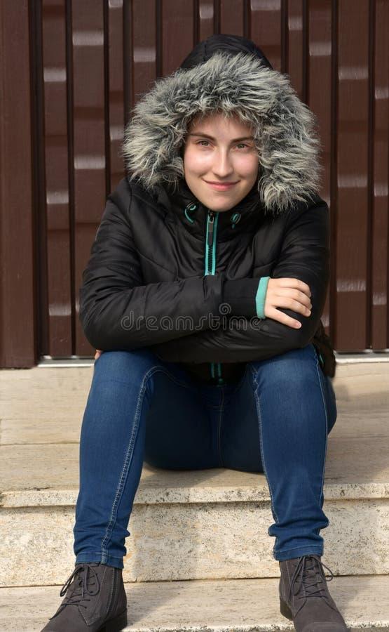 Дружелюбная девушка подростка ждать перед дверью стоковое изображение rf