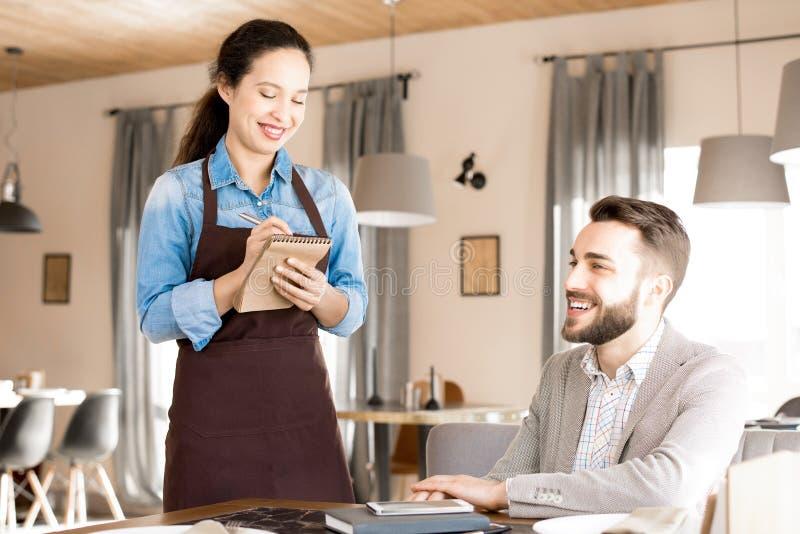 Дружелюбная официантка принимая заказ от клиента стоковое фото rf