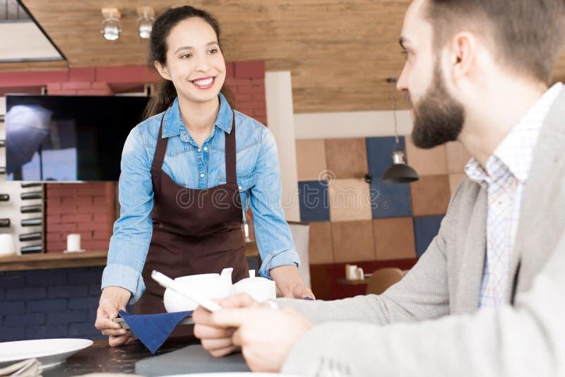 Дружелюбная официантка принося чай к посетителю стоковые изображения