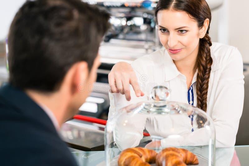 Дружелюбная официантка указывая к французским круассанам в кофе sh стоковые фото